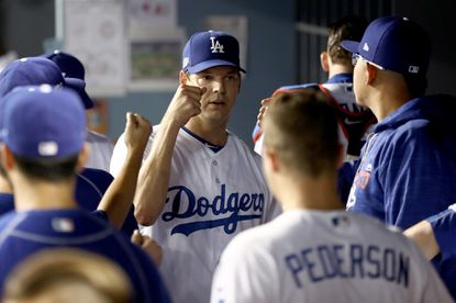 Rich Hill of the Los Angeles Dodgers is greeted by teammates in the dugout while taking on the Chicago Cubs in game three of the National League Championship Series at Dodger Stadium on Oct. 18, 2016 in Los Angeles.