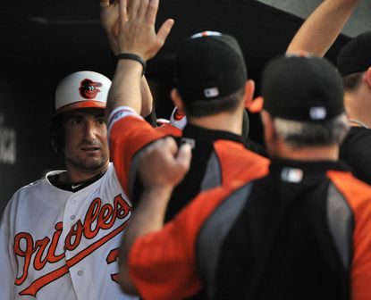 Ryan Flaherty is greeted by teammates after scoring in the third inning against the Nationals.