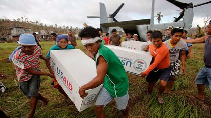 Filipinos carry boxes with aid from the U.S. after an Osprey aircraft of the U.S. Navy landed in a remote village 10 days after one of the most powerful typhoons ever recorded, in 2013.