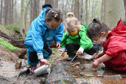 Student with Howard County Conservancy's Nature Preschool, from left, Everly Lewis of Elkridge, Reagan Rogers of Elkridge and Annabel Jones of Crofton, do some exploring in a stream at the Belmont Manor and Historic Park on Saturday, April 10, 2021.