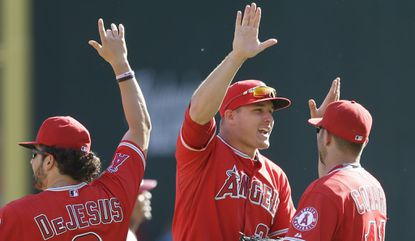 Angels' Mike Trout, center, celebrates with teammates David DeJesus, left, and Kaleb Cowart after an 11-10 win over Texas on Saturday.
