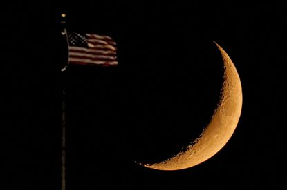An American flag atop the city hall building stands against the setting crescent moon, Sunday, Sept. 20, 2020, in Kansas City, Mo.