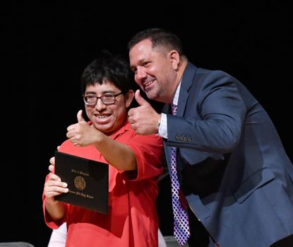 Future Link graduate Jeremy Markovic gives a big thumbs up as he proudly displays his certificate as he poses for a few photos with John Archer School Principal Randy Geyer during the Future Link farewell celebration Friday June 4, 2021 at the Amos Center in Bel Air.