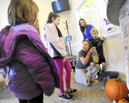 Jenna Handwerger, 7, left, and her sister Lily Handwerger, 10, hand their leftover Halloween candy to dentist Julia Burchett as her son Carter Burchett and dentist Rania Khoury look on at Freedom Dental Care in Eldersburg Saturday, Nov. 1. Children were able to exchange their leftover Halloween candy for a toy at the office Saturday.