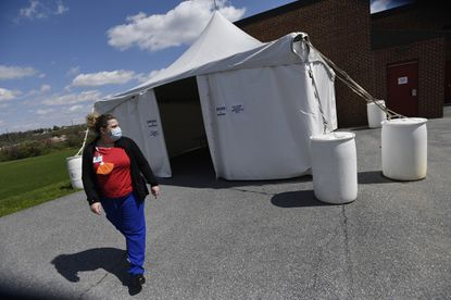 Rebekah Siebe, walks past an intake and screening tent Wednesday, April 15, 2020 at Westminster East Middle School, which has been converted for use as a medical respite for homeless individuals.