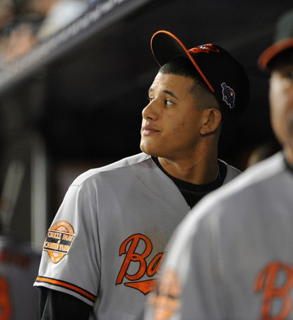 Orioles' Manny Machado walks into the dugout after Raul Ibanez hit the walk-off home run in the 12th inning of Game 3 of the ALDS.