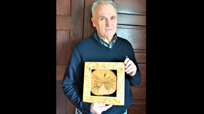 "Fred Nastvogel is pictured with his artwork titled ""Ambrosia.""  The pattern of the framed artwork is created from beetles boring into the tree. He made the frame is from OSB, oriented strand board; wood chips with a binding agent."