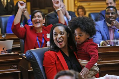 In this Jan 27, 2020, file photo, Virginia Del. Jennifer Carroll Foy holds her son, Alex Foy, as she celebrates the passage of the Equal Rights Amendment in the House chambers at the Capitol in Richmond, Va. The Equal Rights Amendment, finally passed by Congress in 1972 only to stumble during a circuitous ratification effort, still isn't law. But feminist leaders are determined to change that now. (AP Photo/Steve Helber, File)