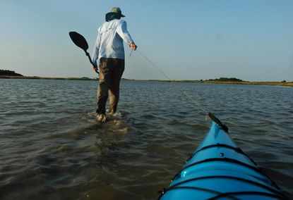 """Author, teacher and former Baltimore Sun writer Tom Horton drags a kayak through shallow water near Smith Island. """"Freedom to Float"""" campaign seeks more sites for boating, fishing, swimming."""