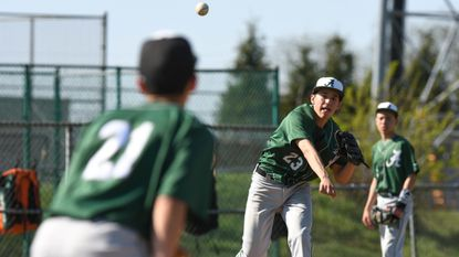 Atholton's Andrew Orlosky throws to first base in an attempt to pick off a Howard runner during a JV baseball game on May 1, 2018.