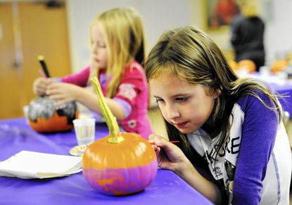 Sisters Emma, 7, right, and Jessica Zinkand, 5, paint Halloween pumpkins at the Eldersburg Branch of the Carroll County Public Library Monday, October 5, 2015.