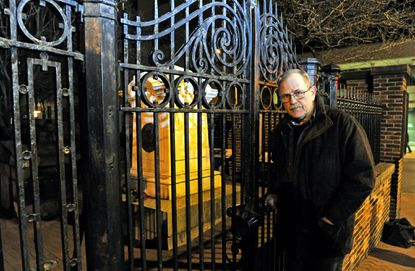 Jeff Jerome, curator emeritus of Baltimore's Edgar Allan Poe House and Museum, stands outside the gates of the Westminster Hall Burying Grounds. Poe is buried under the monument just inside the gates.