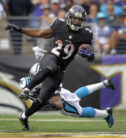 Ravens running back Justin Forsett, front, avoids the tackle attempt by the Carolina Panthers' Bene Benwikere in the second quarter at M&T Bank Stadium.