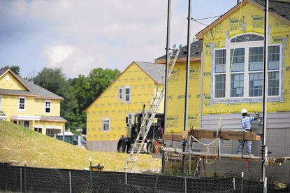 A construction worker attaches siding to a new house being built for Richmond American as part of a new neighborhood of houses in Perry Hall.