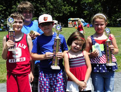 """The top three finishers of last Wednesday's frog jumping contest were, first, Hayden and Ella Celio, center; second , Sage Thorpe and """"Leapster;"""" and third , Kyle and Sam Lynch, left, with """"Jumpy."""""""