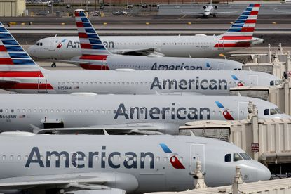 American Airlines jets sit idly at their gates as a jet arrives at Sky Harbor International Airport in Phoenix on March 25, 2020.