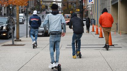 Youths ride rental scooters on the Light Street sidewalk near Pratt Street at the Inner Harbor. The city's proposed new rules forbid riding scooters on sidewalks, except in certain circumstances.