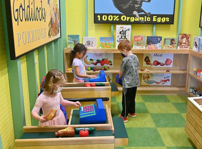 (Left to Right) Helen Rigney, 3, Halethorpe, Zoe Kennedy, 5, Catonsville, and William Rigney, 5 play in the grocery store at Storyville. Storyville, a read and play area for kids age birth to 5, reopened at the two Baltimore County library branches (Woodlawn and Rosedale) on Monday, July 19, 2021. They have been closed since the COVID pandemic took hold last March. Both play-and-learn centers will operate at 50% capacity, allowing a total of 30 children and adults at one time.
