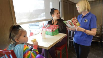 Volunteer Joan Spangler from First Presbyterian Church of Westminster, right, gives Kayla Kelly, of Westminster, and her daughter, Nyla Mallonee, 3, information about Operation Christmas Child boxes at Chick-fil-A in Westminster on Tuesday, Oct. 30, 2018.