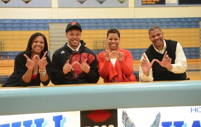 River Hill's Charlie Thomas, second from the left, signed his National Letter of Intent to play basketball at Wisconsin on Friday. He was joined by his sister Taylor Thomas, left, mother Deanna Thomas, second from right, and father Charlie Thomas.