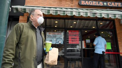 Ken Mills stands in front of Towson Hot Bagels after picking up his coffee and lunch order from the makeshift pick-up window at the restaurant in Towson on Wednesday, April 8.
