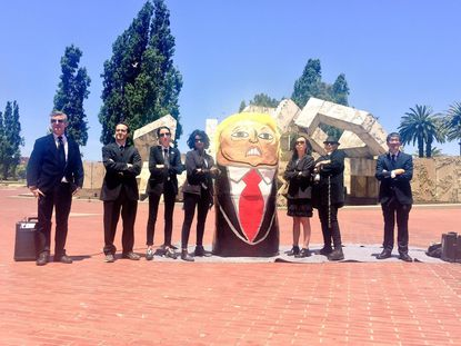 SF March for Truth protest organizers dressed as FBI agents stand next to paper mache Trump Russian doll at Justin Herman Plaza.