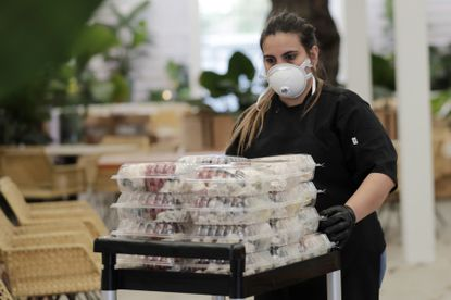Chef Liset Garcell prepares to give out free meals at the Red Rooster Restaurant in Miami earlier this month, in partnership with World Central Kitchen. World Central Kitchen is now distributing meals to families at 10 Baltimore City schools. (AP Photo/Lynne Sladky)