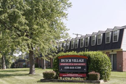 A sign sits outside the Dutch Village apartments and townhomes in Baltimore, owned by the Kushner Cos. Jared Kushner's family real estate firm owns thousands of apartments and townhomes in the Baltimore area, and some have been criticized for the same kind of disrepair and neglect that the president has accused local leaders of failing to address. (AP Photo/Steve Ruark)