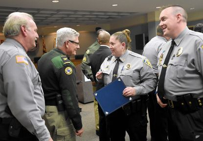 Crisis Intervention Team member Sgt. Nicole Ensor, of the Westminster Police Department, shows her newly received pin to McDaniel College Department of Campus Safety Chief Mike Webster and Westminster Police Department Major Ron Stevens as fellow team member PFC Christopher Obst, of the Westminster Police Department, looks on Friday, Nov. 21 in Westminster.