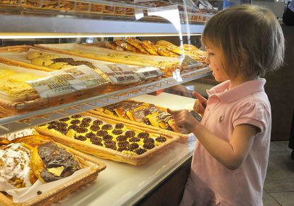Caroline Hirsch, 3, of Baltimore, examines the pastries at Goldberg's New York Bagels, which are not eaten during Passover by observant Jews.