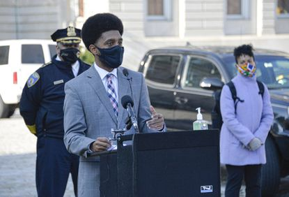 Mayor Brandon M. Scott provides an update on Baltimore's response to the COVID-19 pandemic along with Baltimore Police Commissioner Micheal Harrison, left, and Baltimore City Health Commissioner Dr. Letitia Dzirasa, right, in front of City Hall on Dec. 11.