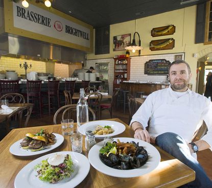 Brendan Keegan poses with some of the food served at Brasserie Brightwell in downtown Easton.