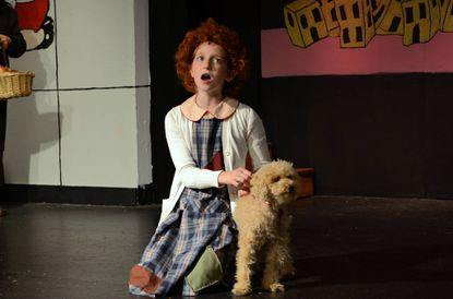 """Samantha Yakaitis, as Annie, sings to Sandy, a canine actor whose actual name is Graham, in Laurel Mill Playhouse's current production of """"Annie."""""""