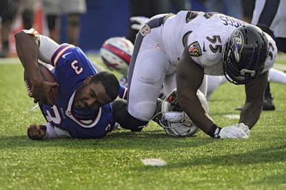 Ravens linebacker Terrell Suggs, right, hits Buffalo Bills quarterback EJ Manuel late in the fourth quarter, knocking his helmet off. Suggs was called for a penalty on the play.