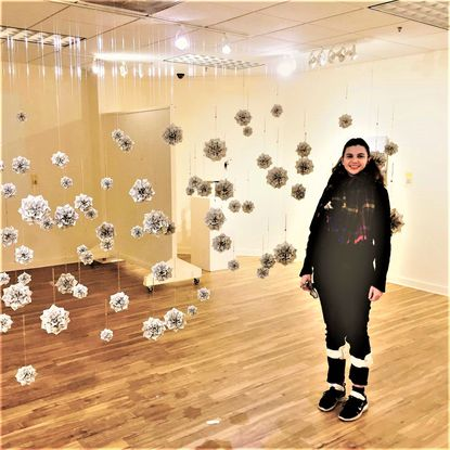 """Local minister and artist Becca Crate is pictured with her installation the """"Hymnal Collective"""" that was on exhibit at the Carroll County Arts Council in the juried show """"To the Tune of…"""""""