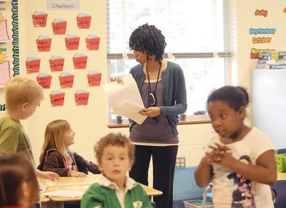 "West Towson Elementary School first-grade teacher Amber Varlack hands out homework during her morning lessons on April 30. Varlack's students take breaks using a program called ""Adventure To Fitness"" that inspires kids to move and learn at the same time. Varlack won an award for using this activity with her students."