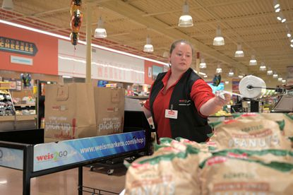 Weis 2 Go personal shopper Brittany Vagenos uses a cart to retrieve items for an online shopper at the Nottingham Weis market in August.