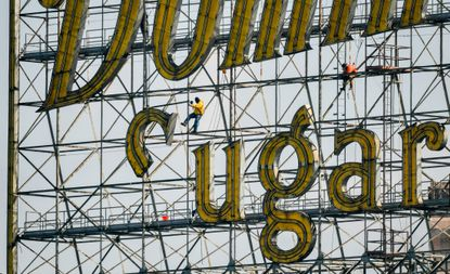 """Workers from Anderson Industrial Contracting lower the top half of the """"S'""""in """"Sugars"""" from the Domino Sugars sign in Tide Point. The iconic neon sign that has been part of the landscape of Baltimore's Inner Harbor since 1951 is being replaced with a more efficient LED version."""