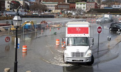 A truck drives through water covering Dock Street as well as portions of the City Dock construction site in Annapolislast month.