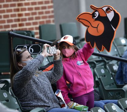 WIth her mother Amy Calvin, Payton Calvin, 9, waves a foam oriole during the Baltimore Orioles' home opener against the Boston Red Sox at Oriole Park at Camden Yards Thursday, April 8, 2021. (Dylan Slagle/Carroll County Times).