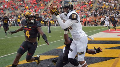 Towson wide receiver Jabari Allen makes a catch between Maryland defensive backs Darnell Savage Jr. (4) and Antoine Brooks to score the team's first touchdown during a game earlier this season.