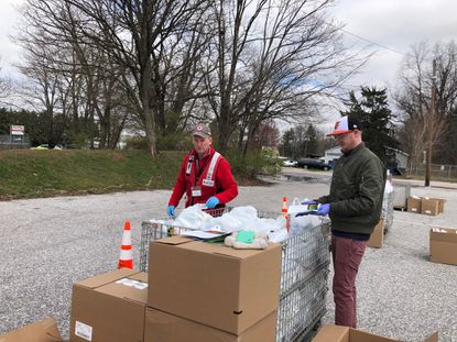 David Benedict and Jacob Hill prepare to distribute food to Carroll Food Sunday clients on Thursday, March 26.