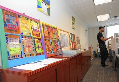 Baltimore, MD- 6/11/13- Marcus Dixon, 30, talks to a responsible fatherhood specialist at the Center for Urban Families In the foreground is artwork created by fathers and their children. Algerina Perna/Baltimore Sun, #4241.