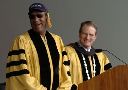 Entertainer Bill Cosby speaks during the 2004 commencement at Johns Hopkins University. At right is then-Hopkins President William R. Brody.
