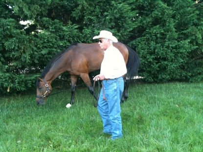 Trainer D. Wayne Lukas walks Optimizer after arriving Tuesday at Pimlico Race Course.