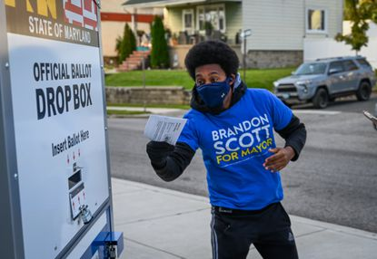 Democratic mayoral candidate Brandon Scott playfully lunged toward a ballot drop box Nov. 3, 2020, before depositing his ballot outside Forest Park High School.
