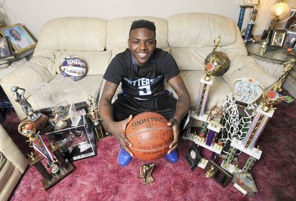 Basketball phenom Aquille Carr of Patterson High School, who many scouts consider the best high school player in the United States, is pictured in his Baltimore home with several of his trophies.