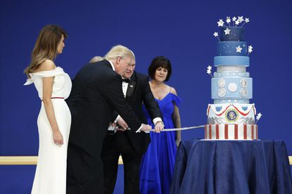 First lady Melania Trump watches as President Donald J. Trump and Vice President Mike Pence are helped by Coast Guard Petty Officer 2nd Class Matthew Babot as they cut a cake at the Salute To Our Armed Services Inaugural Ball on Friday, Jan. 20, 2017, in Washington. Karen Pence watches at right.