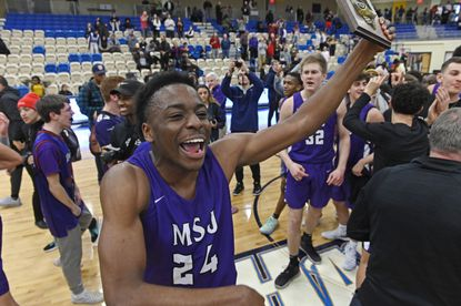 Mount Saint Joseph's Jason Edokpayi celebrates with the championship plaque after defeating St. Frances to win the MIAA A Conference boys basketball title at APGFCU Arena at Harford Community College on Feb. 23, 2020.