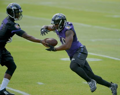 Ravens quarterback Josh Johnson hands off to running back Kenneth Dixon during minicamp at the Ravens' training facility.